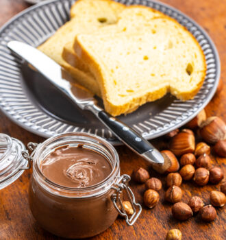 Hazelnut spread and toast bread. Chocolate cream on wooden table.